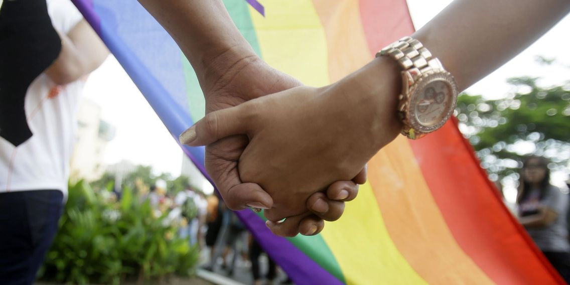 LGBT & LGBTQ flag MTF M2F hand holding with gender fluid, transexual & bisexual people nearby