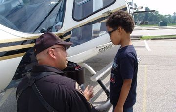 Police helicopter pilot talking to a little boy.