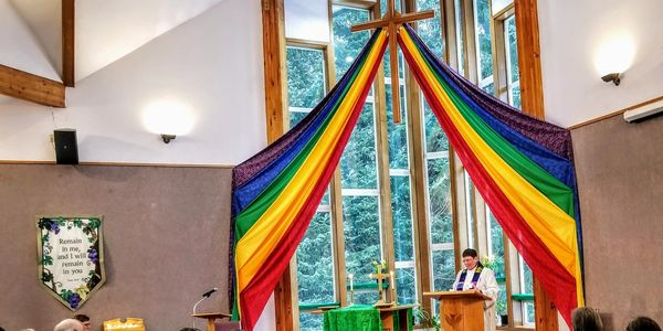 Pride rainbow banner draped from cross with Pastor Karen Dammann at pulpit