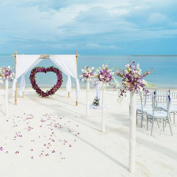 Beach setting with floral heart backdrop for Humanist wedding with English Celebrant Susan Dobinson