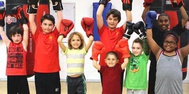 Several young kids with their hands up in boxing gloves, smiling.
