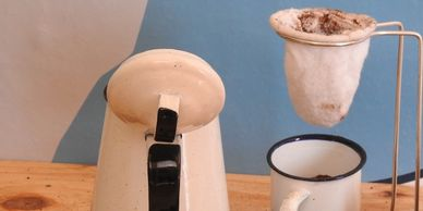 coffee pot, cloth coffee filter over cup with coffee beans