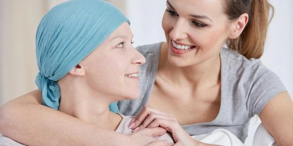 Young woman comforting a cancer patient by wrapping her arm around her.