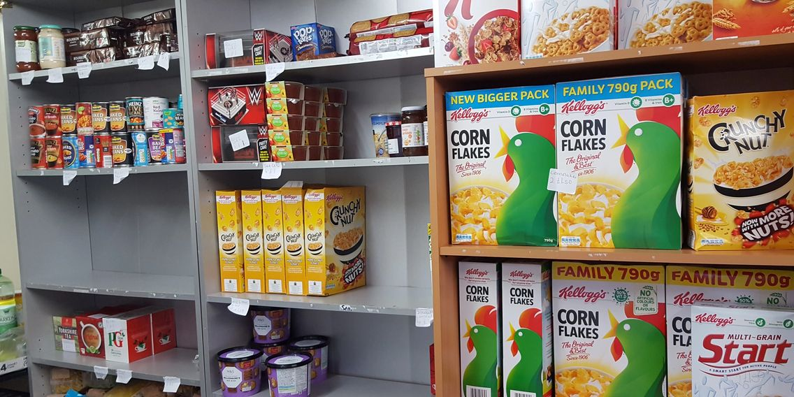 Shelves stocked with food, corn flakes, cereal, tea, jars