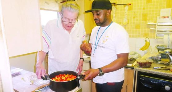 Young man helping older man cook