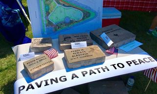 The photo shows a variety of paver blocks with messages engraved on them.