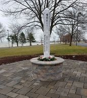 The Peace Pole is in the center of the Peace Patio. It is surrounded by paver blocks.
