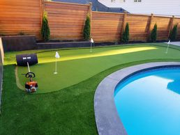 Artificial lawn putting green by pool