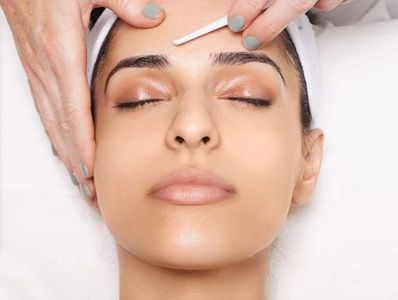Women receiving a dermaplane treatment on her forehead.