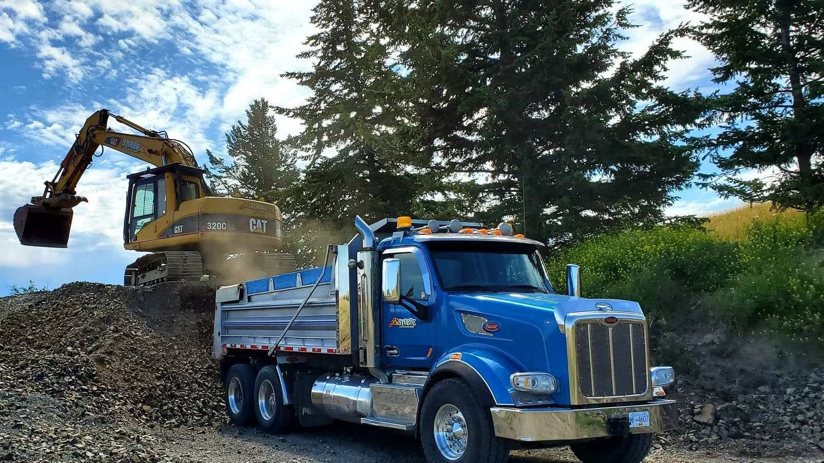 Stobbe Excavating Cat excavator loading Peterbilt dump truck with rock