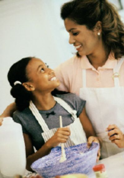 Mother and Daughter enjoy making dinner in their kitchen.
