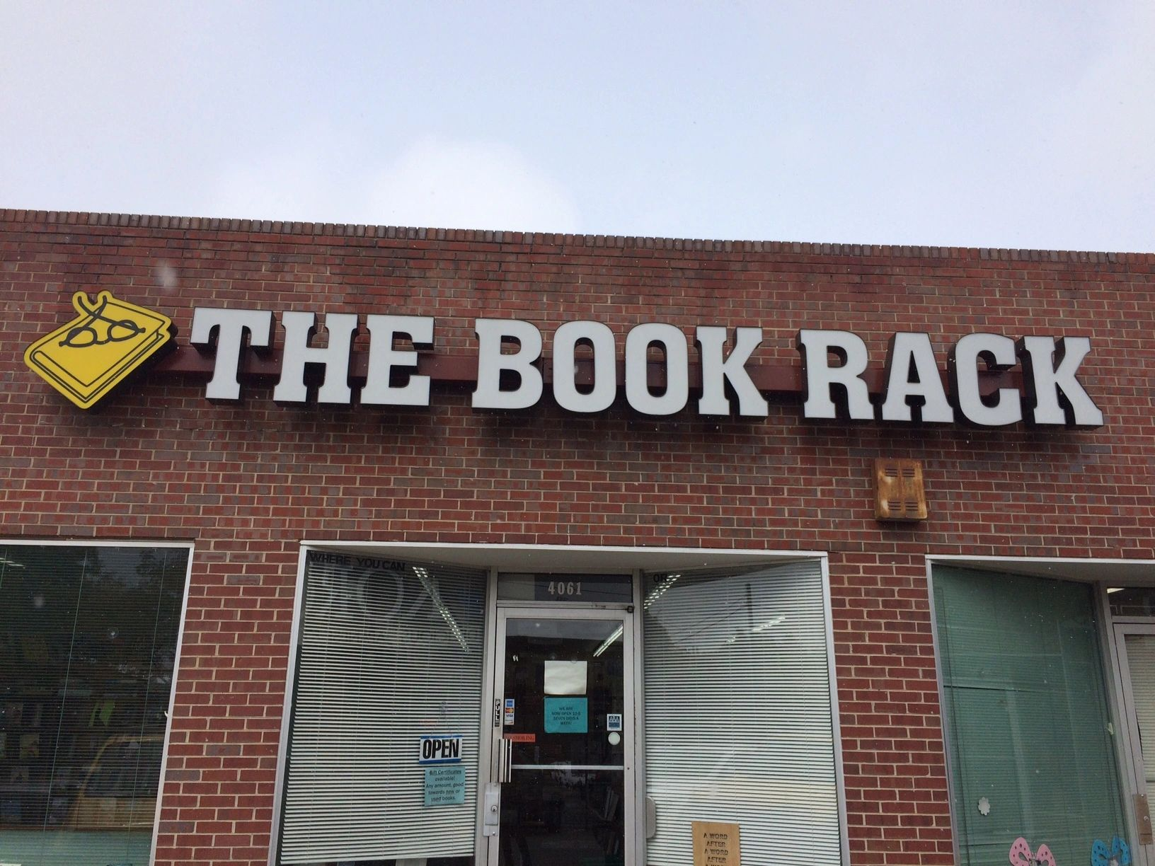 Photo of storefront with sign for The Book Rack