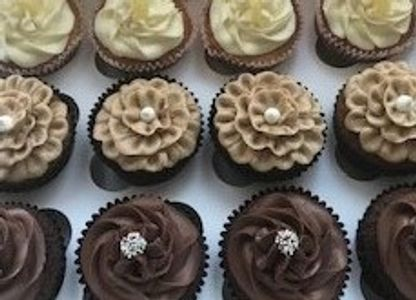 lemon caramel and chocolate cupcakes decorated with piped swirls and flowers