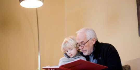 Grandpa reading with little girl under LED Lightbulb