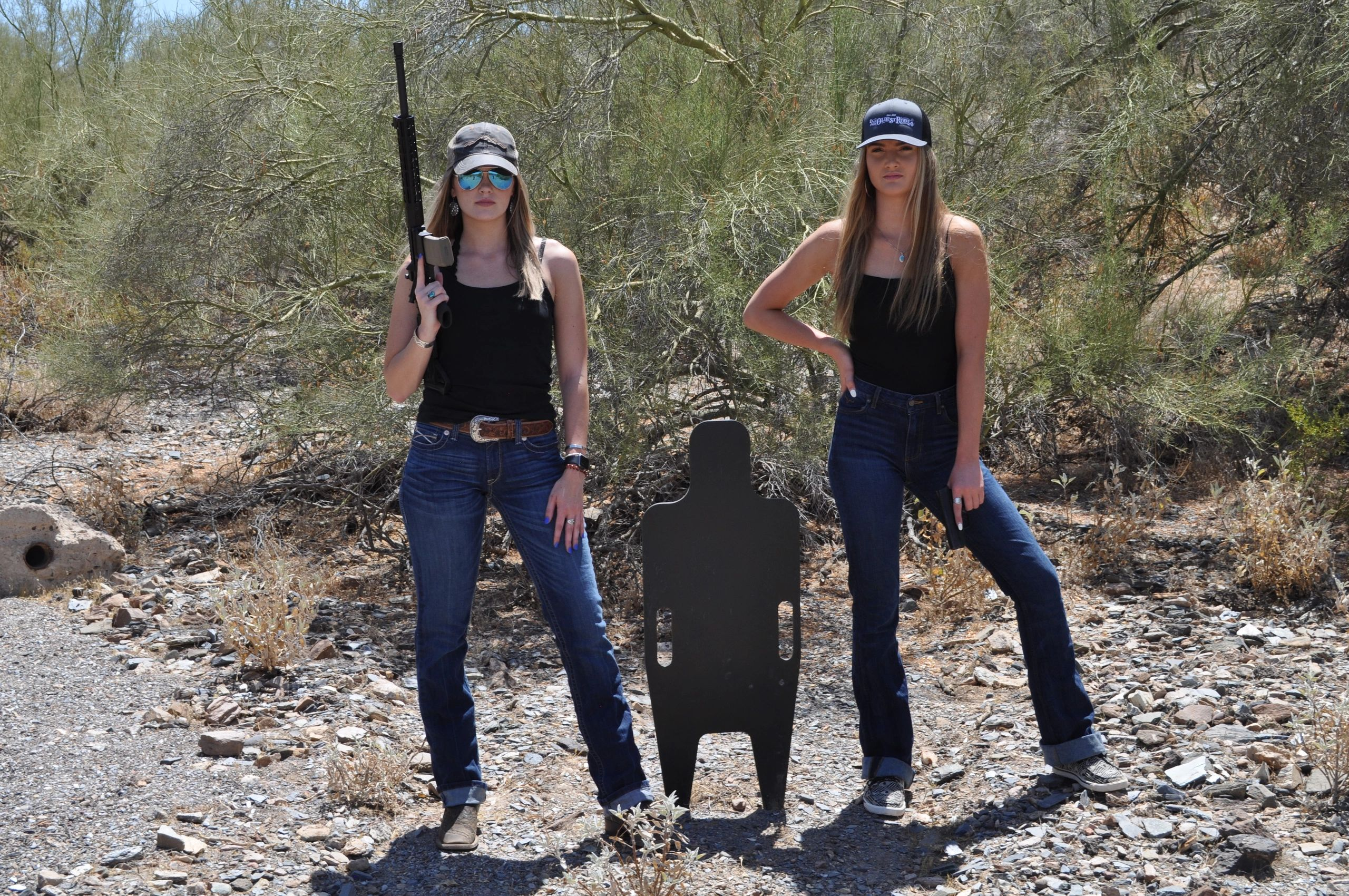 Two women in tank tops with guns and a steel target