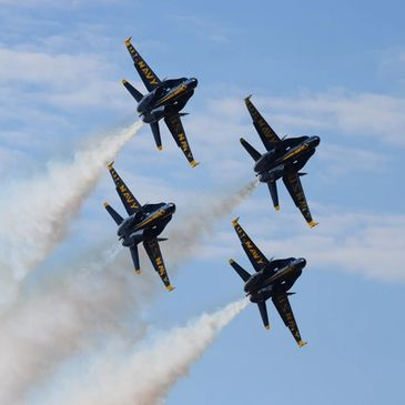 Four Blue Angels, the U.S. Navy flight demonstration team, turning toward the camera.