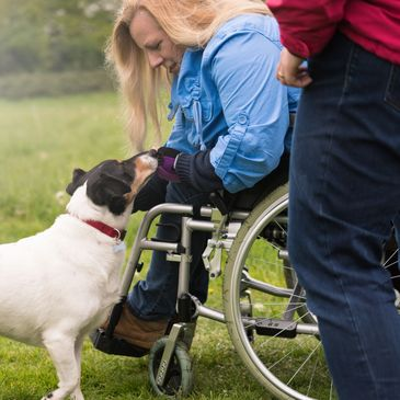 Woman in a wheelchair talking to her dog while outside.