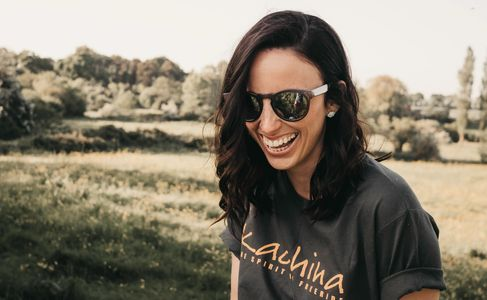 Smiling woman with grey Kachina t-shirt in a countryside setting.