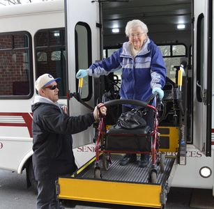 A passenger is assisted off of a township bus.