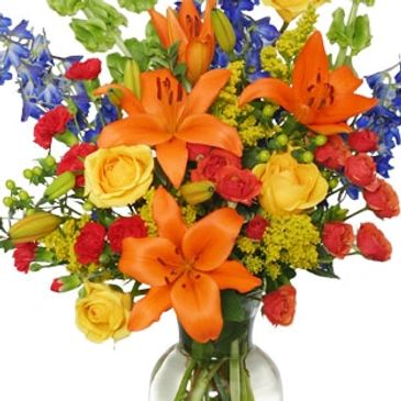 Tall fall arrangement of lilies and blue delphinium with vibrant fall color blooms
