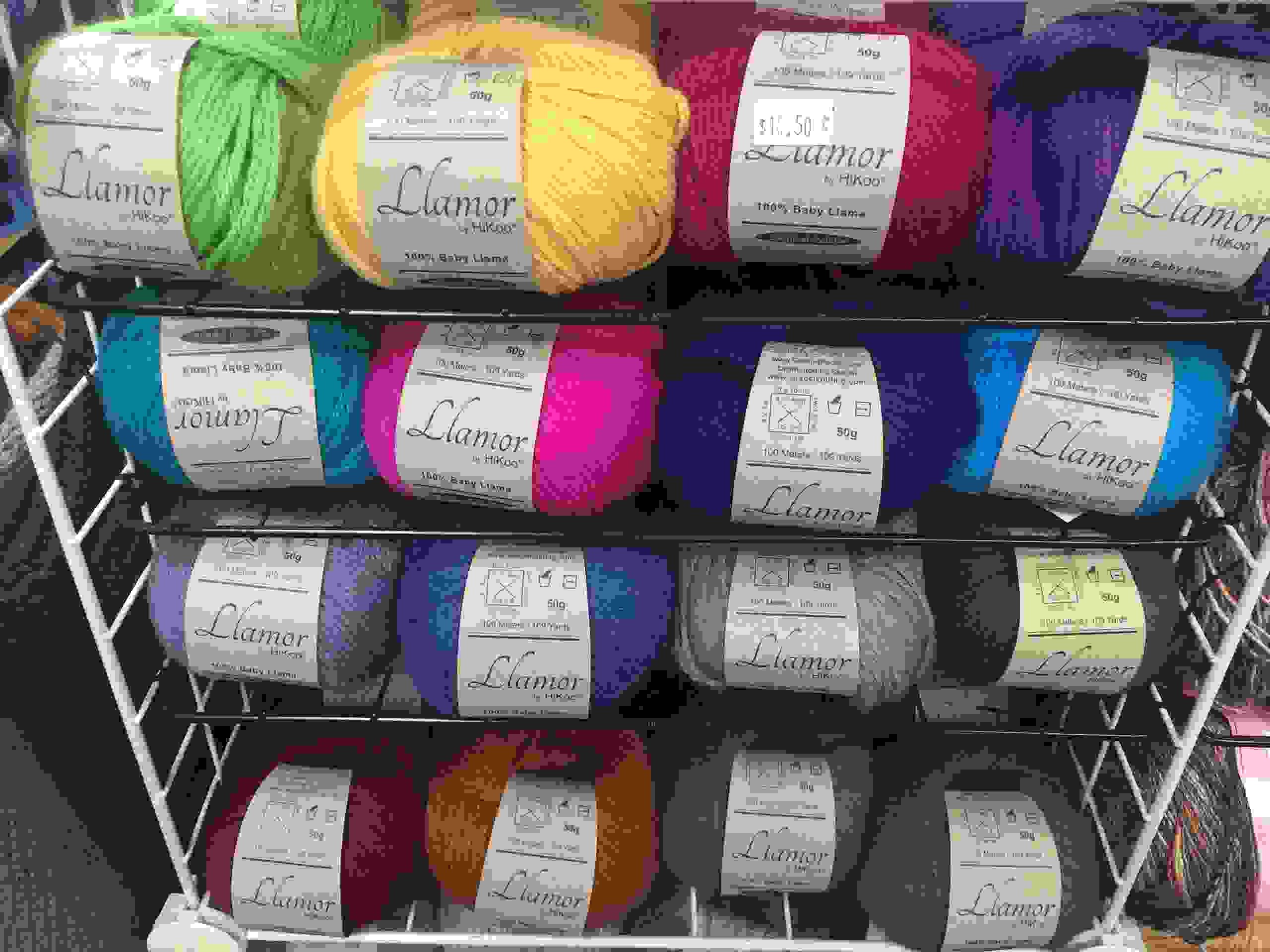 balls of yarn on shelves in various colors
