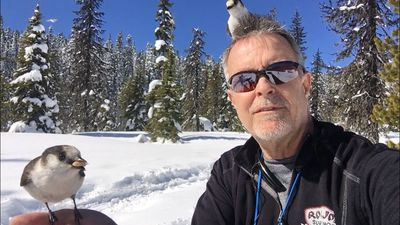 David W. Brown feeding new friends while  snowshoeing on Mt. Hood, Oregon.