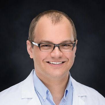 Dr. Jeremy Goetsch wearing a white lab coat and glasses