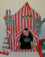 Boy takes a picture in our circus prop for photos while theme games are played with the Houston kids