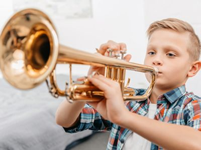 Boy playing a trumpet at the Norman Music Institute