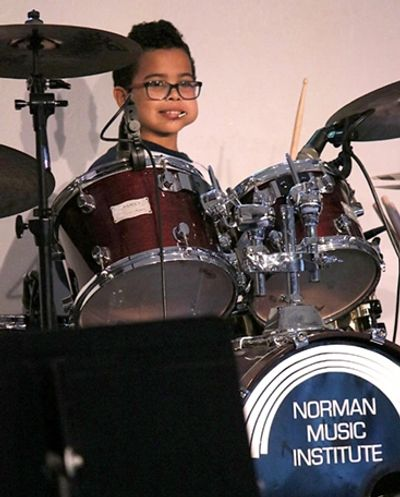 Young Male learning to play Drums at the Norman Music Institute
