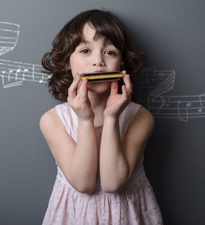 Young Female learning to play the Harmonica at the Norman Music Insitute