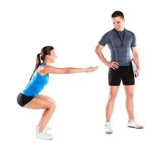 Personal Trainer Training a client performing an exercise and doing a workout
