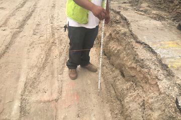 Subgrade inspection.  A man stands with a tape measure to check the depth to subgrade.