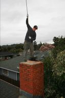 Mike the local business owner of Clean-Rite Chimney Cleaning performing a chimney sweep