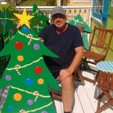 Steve Fox shows off his artistic flair with one of the Christmas Trees he painted for display in Cry