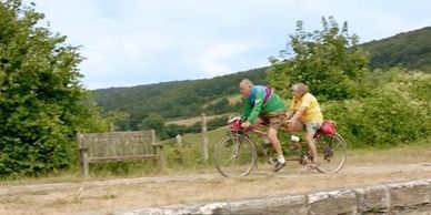 A man and a woman on a tandem bike riding through the countryside