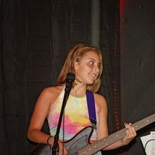 girl and guitar in front of a microphone on stage