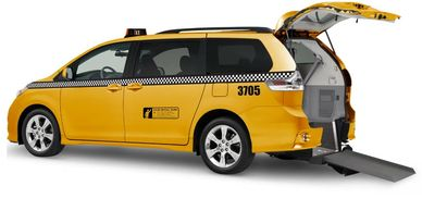 Image of an accessible yellow mini-van taxi with rear entry ramp.