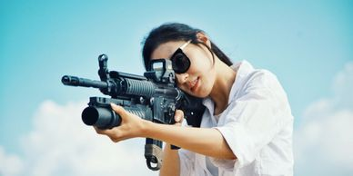 Woman with sunglasses pointing a rifle