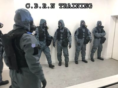 Operatives in protective CBRN gear on training exercise. Training for potential risks and hazards.