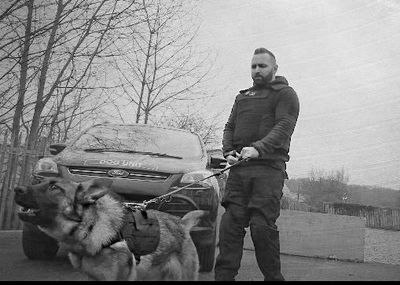 Security dog handler and his German Shepherd security dog, standing in front of a K9 Unit vehicle.