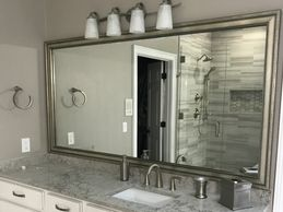 Grecian style mirror frame coordinates wonderful with brushed nickel bathroom hardware!