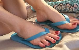 The nicely arched red toed feet of Miss Zoe Kate in some blue flip flops.