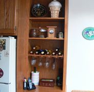 Cabinet to match existing kitchen. Adjustable shelves and wine rack with glass holder.
