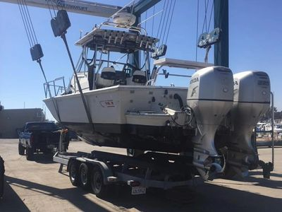 Twin BF250 Honda outboards coming in for service.  Boston Whaler is being hoisted onto boat trailer.