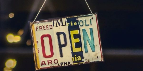 "Picture of an ""open"" sign made from old car license plates."