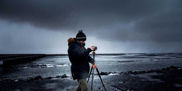 picture of a man taking pictures on a cold beach.
