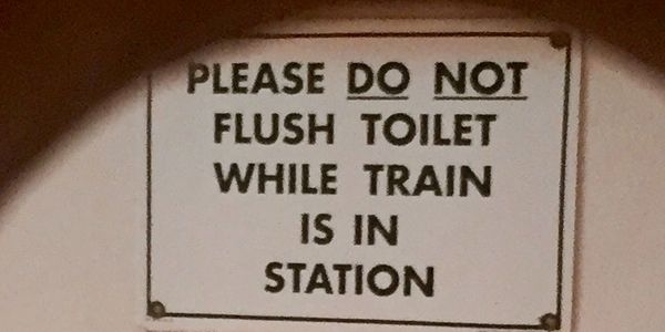 Sign that says: Please do not flush while in train station.