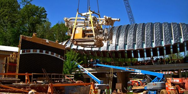 A crane lowering FS GEOCON Beretta T41 rock drill into place during construction of Crystal Bridges.