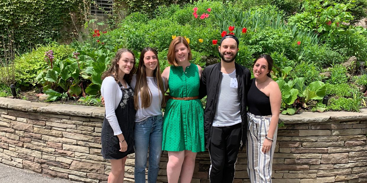 Taylor Medeiros, Anna Zappone, Emma Graham, Adam Gomes, and Jessica Sorbara pose together in front of a bed of flowers outside Brennan Hall.
